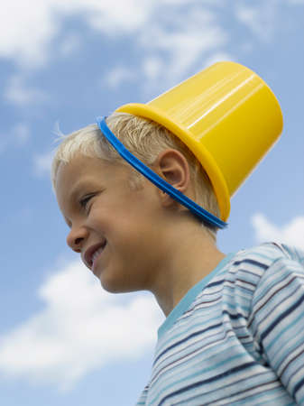 head in the sand: Close-up of a boy smiling with a sand pail on his head