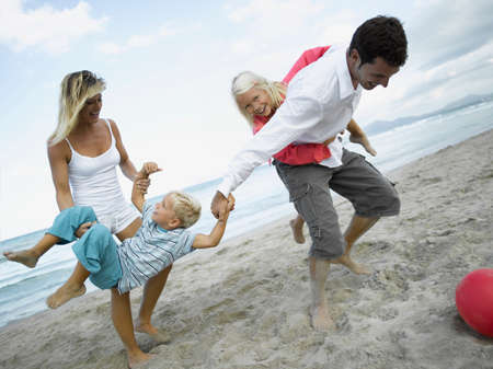 mid adult couple: Mid adult couple and their children playing on the beach LANG_EVOIMAGES