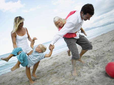 mid adult couple: Pareja de mediana edad y sus hijos jugando en la playa LANG_EVOIMAGES