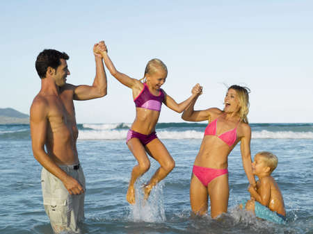 barefoot teens: Mid adult couple and their two children in the sea