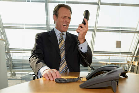 telephone receiver: Businessman holding a telephone receiver and shouting LANG_EVOIMAGES
