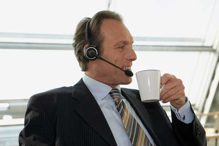 receding hairline: Close-up of a businessman wearing headset and holding a cup of tea LANG_EVOIMAGES