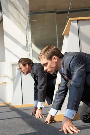 starting line: Side profile of two businessmen crouching at a starting line