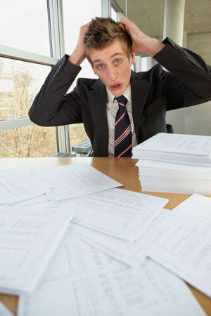 overburdened: Businessman sitting with documents and looking worried
