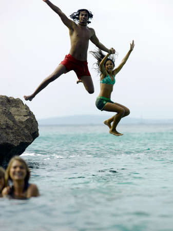 swimming shorts: Young couple holding hands and jumping in water