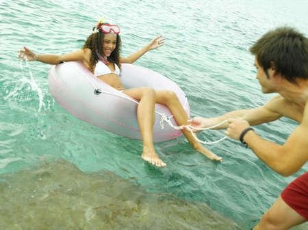 swimming shorts: Young man pulling a life belt with a young woman lying on it