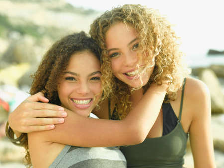 female bonding: Portrait of two young women smiling with their arms around each other