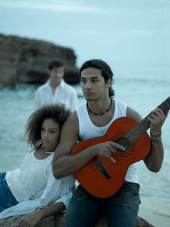 fully unbuttoned: Young man playing the guitar with a young woman looking away LANG_EVOIMAGES