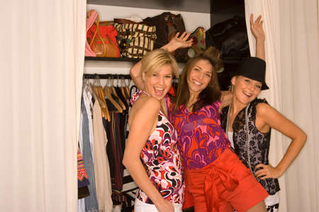 hot pants: Portrait of three young women standing in front of a closet and smiling