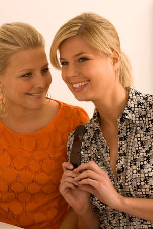 flip phone: Close-up of two young women smiling