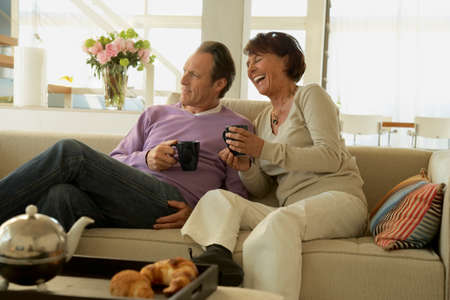 legs crossed on knee: Mature couple sitting on a couch and holding cups of coffee LANG_EVOIMAGES