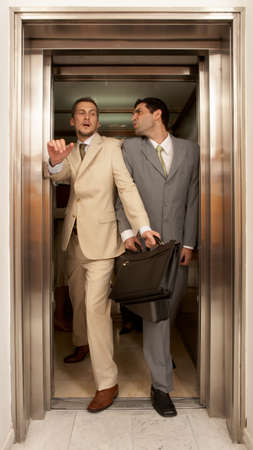 business rival: Two businessmen struggling to get out of an elevator LANG_EVOIMAGES