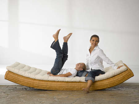 female bonding: Mid adult woman sitting and her daughter lying down on a rocking bed LANG_EVOIMAGES