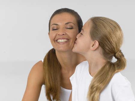 female bonding: Girl kissing her mother