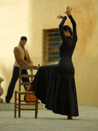 Perfil lateral de un baile del bailarín de sexo femenino con un hombre joven con una guitarra en el fondo LANG_EVOIMAGES