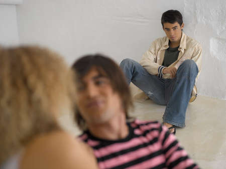 only three people: Young man leaning against a wall in front of a young couple