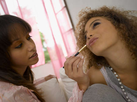 puckering lips: Close-up of a young woman applying lipstick on her friend