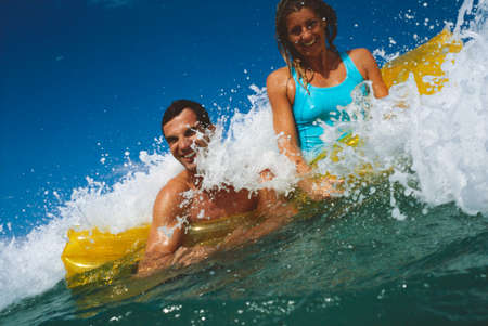 mid adult couple: Mid adult couple on an inflatable raft in the sea