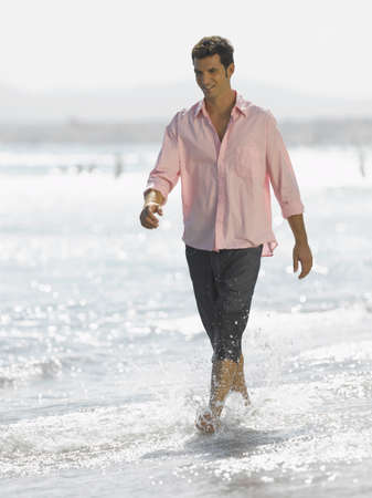 rolled up sleeves: Mid adult man walking on the beach