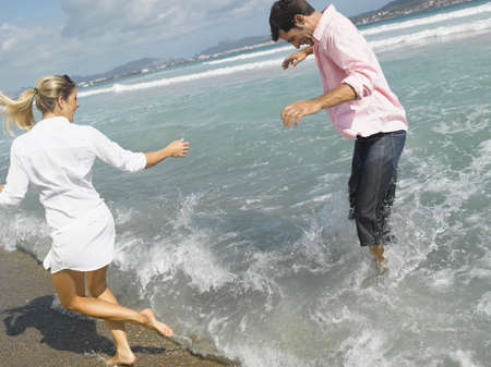 mid adult couple: Mid adult couple splashing water on the beach LANG_EVOIMAGES