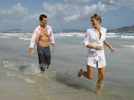 fully unbuttoned: Couple running on the beach