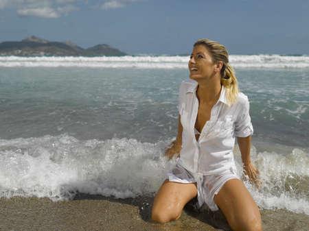 mujer arrodillada: Mujer adulta mediados de rodillas en la playa LANG_EVOIMAGES