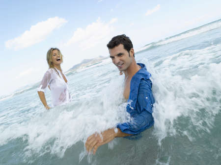 waist deep: Mid adult couple splashing water in the sea