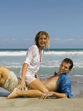 rolled up sleeves: Mid adult couple smiling on the beach LANG_EVOIMAGES