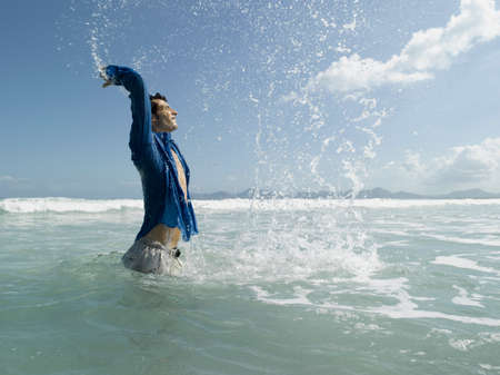 one mid adult man only: A man splashing water in the sea