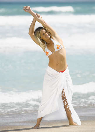 only mid adult women: A woman standing on the beach with her arms raised