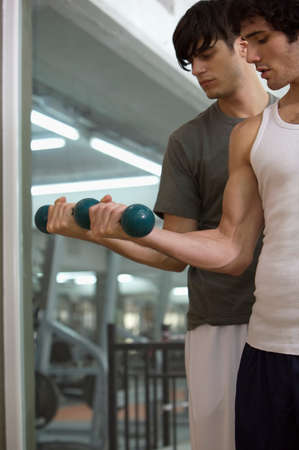 men exercising: Two young men exercising with dumbbells in a gym
