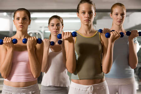 body concern: Four young women exercising with dumbbells in a gym