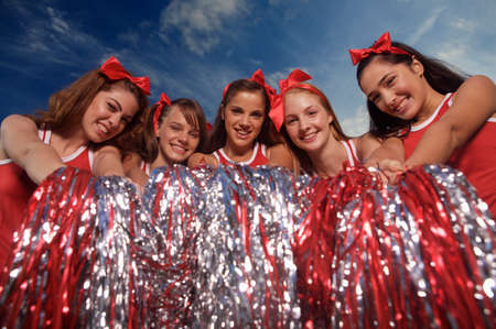 adult cheerleader: Portrait of five cheerleaders holding pom-poms and smiling