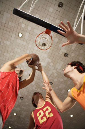 young men: Low angle view of three young men playing basketball LANG_EVOIMAGES