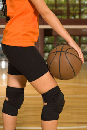 kneepad: Mid section view of a female basketball player holding a basketball