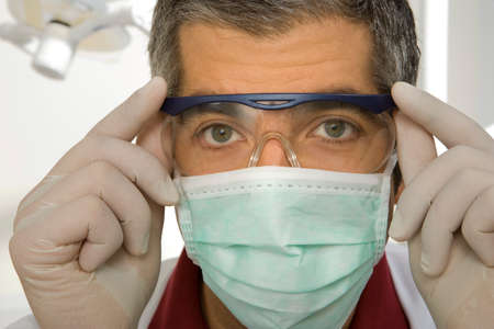 protective eyewear: Portrait of a male dentist adjusting his protective eyewear