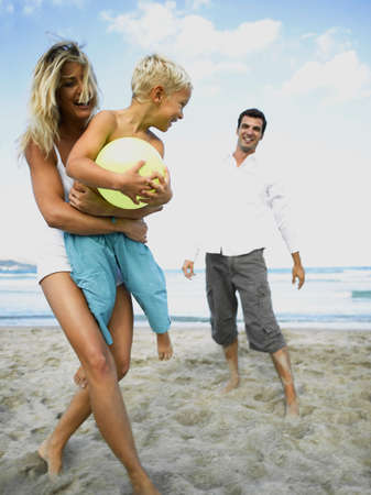 two piece swimsuits: Woman holding her son with a man standing behind him on the beach