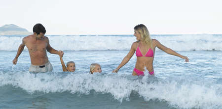 mid adult couple: Mid adult couple and their children in the sea LANG_EVOIMAGES