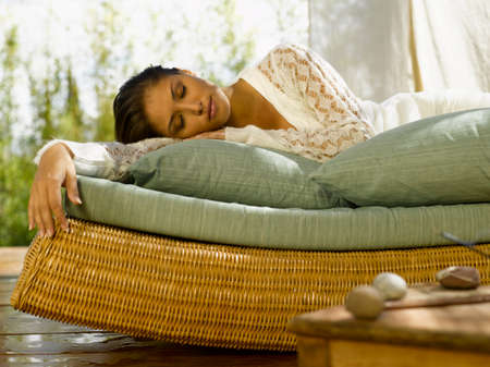 chaise lounge: Young woman lying on a chaise lounge with her eyes closed LANG_EVOIMAGES