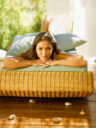 chaise lounge: Portrait of a young woman lying on a chaise lounge and smiling