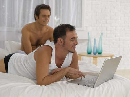 two people only: Young man lying on the bed and using a laptop LANG_EVOIMAGES