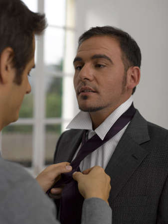 adjusting: Close-up of a young man adjusting a young mans tie