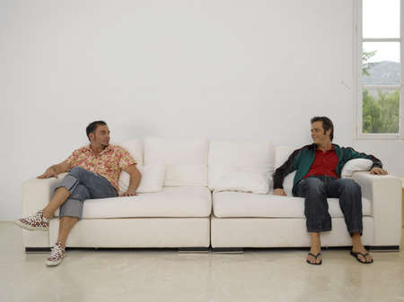 short sleeved: Two young men sitting on a couch and looking at each other LANG_EVOIMAGES