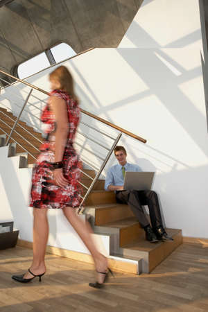 hand rail: Businessman sitting on a staircase and using a laptop while young woman passing by him