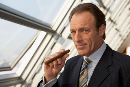 receding hairline: Close-up of a businessman holding a cigar LANG_EVOIMAGES