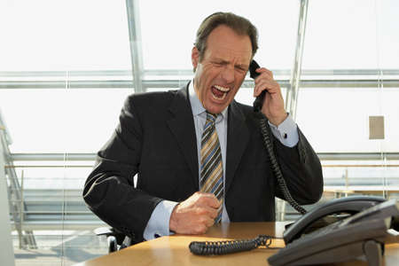 receding hairline: Businessman talking on the telephone and shouting LANG_EVOIMAGES