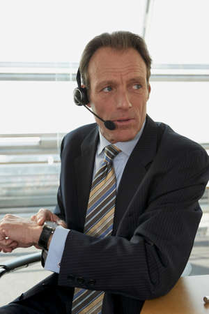 receding hairline: Close-up of a businessman wearing headset and checking the time LANG_EVOIMAGES