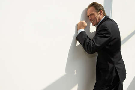 irritated: Side profile of a businessman leaning against a wall and looking irritated