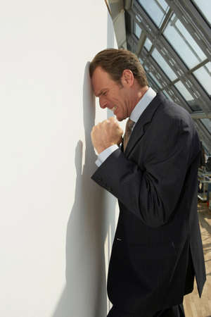 receding hairline: Side profile of a businessman leaning against a wall and looking irritated