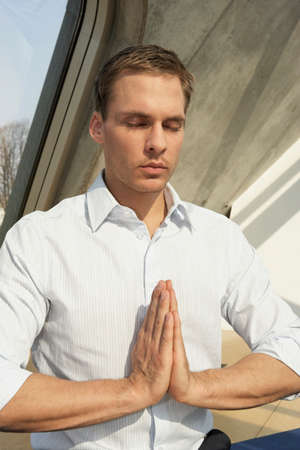 rolled up sleeves: Businessman meditating in an office LANG_EVOIMAGES